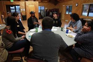 Group of people working together around a small round table insde a room with wood paneled walls