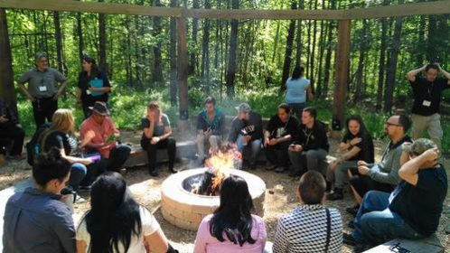 Group photo of people sitting around a campfire in the woods